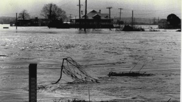 A flood level indicator at the Windsor Bridge and a building in the middle of the Hawkesbury River surrounded by raging flood waters, August 7, 1986.