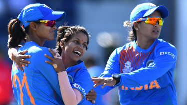 Poonam Yadav is mobbed by teammates after snaring a wicket against Sri Lanka.