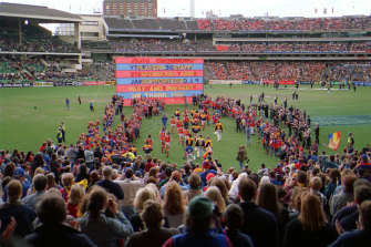 Players run onto the ground for Fitzroy's farewell game at the MCG.
