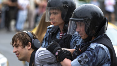 Police officers detain a protester during a march in Moscow, Russia.