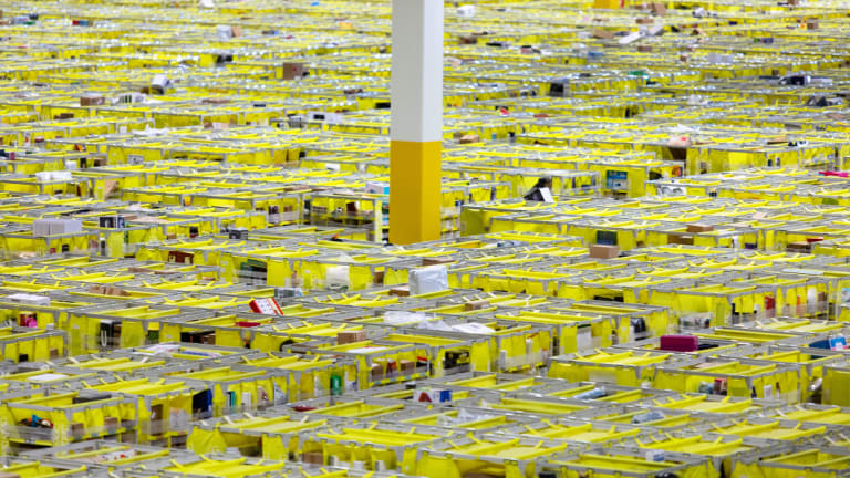Shelves with products are organised and moved around by orange Amazon robots inside the Amazon Fulfillment Center in Carteret, New Jersey.