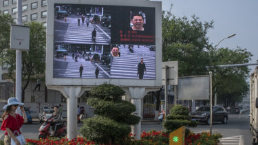 A road in Xiangyang, China equipped with facial recognition technology, displays photos of jaywalkers alongside their name and identification number.