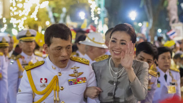 King Maha Vajiralongkorn and Queen Suthida wave to supporters in Bangkok, Thailand.