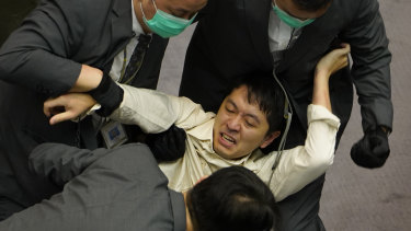 Ted Hui, a pro-democracy lawmaker, is removed by security officers during scuffles between pro-establishment and opposition lawmakers.