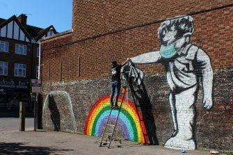 """Street artist Chris Shea works on his 100th 'Rainbow Boy' artwork in West Wickham, south London. Forty-eight per cent of Britons have been """"accepting"""" of the lockdown."""