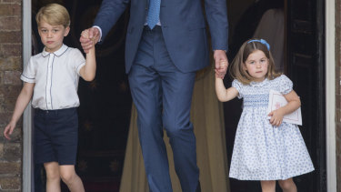 Prince George and Princess Charlotte holding onto their father Prince William's hands as they leave the chapel.