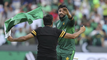 A fan runs onto the field to congratulate Imad Wasim.
