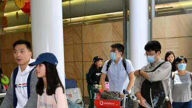 Passengers wearing protective masks arrive at Sydney International Airport in Sydney.