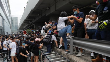 Pro-democracy protesters leave after riot police arrive outside the airport in Hong Kong.