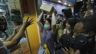 A protester throws a box of goods at a store that sells to mainland customers in Hong Kong.
