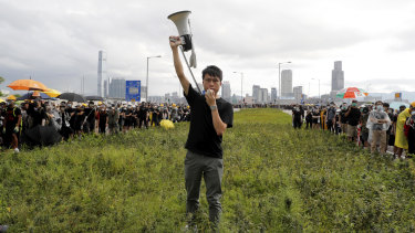 Hong Kong pro-democracy lawmaker Roy Kwong speaks over a loud hailer to the police as he joins protesters on July 1.