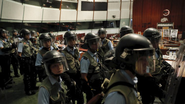 Police officers with protective gear retake the meeting hall of the Legislative Council in Hong Kong early on Tuesday.