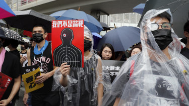 Protesters, some wearing eye patches to show solidarity to a woman reportedly injured in the eye by a beanbag fired by police, hold up a banner that reads 'We are not targets'.