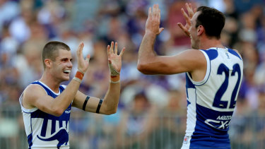 Off the mark: Bailey Scott (left) celebrates with Todd Goldstein after scoring for North Melbourne on debut.