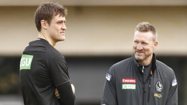 Injured Magpie Darcy Moore (left) with coach Nathan Buckley.