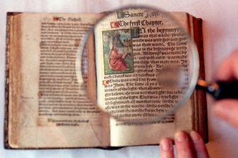A magnifying glass highlights the precise script and illustrations in the only complete extant copy of the 1526 edition of William Tyndale's translation of the New Testament.