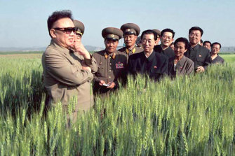 North Korea's then leader Kim Jong-il, left,  visits a farm with officials in 2003.
