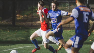 Canberra's Matthew Waters and Olympic's Nathan Megic jostle for the ball.