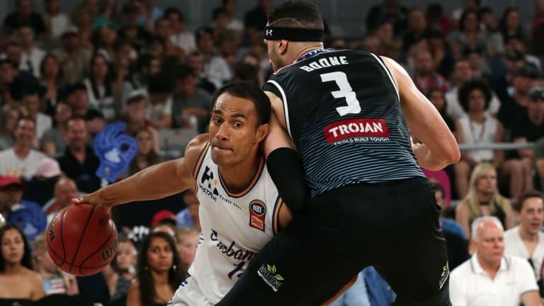 Solid Defense: Mika Vukona from Brisbane Bullets tries to get around Melbourne, Josh Boone.