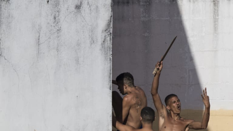 Gangs have a lot of sway in Brazil's prisons. Here, inmates display a makeshift knife moments after police left the prison in the Alcacuz prison in Nisia Floresta, near Natal, Brazil during an uprising in 2017.