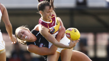 Charlotte's web: Brisbane's Jade Ellenger is caught up in a tackle by Blues' Charlotte Wilson.
