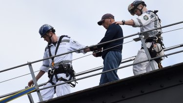 NSW police officers guide the man off the Sydney Harbour Bridge.