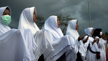 Indonesian women attend a prayer for the victims of the September 28 earthquake and tsunami on Talise Beach in Palu, Central Sulawesi, Indonesia, on Friday.