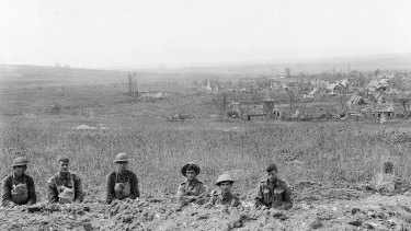 Australian and American troops in a trench after the Battle of Hamel with the village, then freed of Germans, behind them.