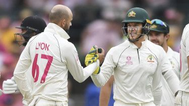 Nathan Lyon is congratulated by Tim Paine after taking five wickets at the SCG on Sunday.