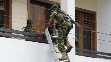 Sri Lankan police commandos enter a suspected hideout of militants following a shootout in Colombo.