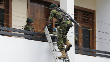 A Sri Lankan police commando enters a house suspected to be a hideout of militants following a shoot out in Colombo, Sri Lanka on Sunday.