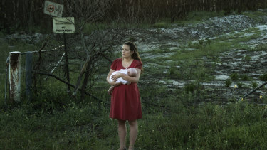Samantha Kelly with her baby William near one of the contaminated drains near RAAF base Williamtown.