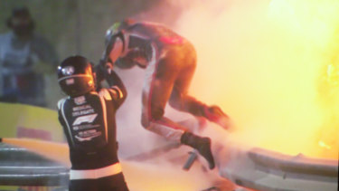 Romain Grosjean is helped from his burning car.