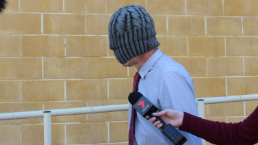 Simon Squires leaves Burwood Local Court with a beanie over his face.