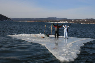 Two fishermen use a smaller piece of ice as a raft and try to row to land.
