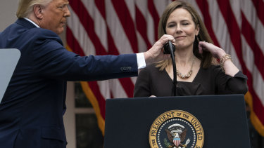 President Donald Trump adjusts the microphone after he announced Judge Amy Coney Barrett as his Supreme Court nominee in September.