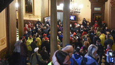 People protest outside the entrance of the Michigan House of Representatives in Lansing, Michigan.