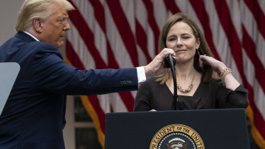 President Donald Trump adjusts the microphone after he announced Judge Amy Coney Barrett on Saturday.
