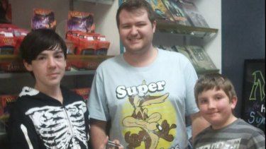 Brisbane's last video store owner Brenton Snell with customer, Remus (left) and James.