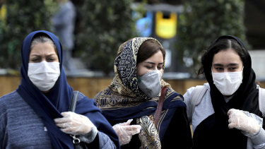 People wear masks to help guard against the Coronavirus on a street in downtown Tehran, Iran.