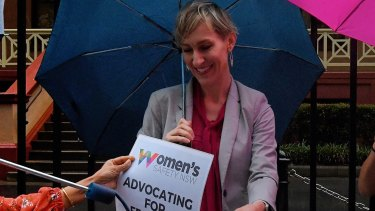 Women's Safety NSW chief executive Hayley Foster holds up a sign at a rally in Sydney against domestic violence.