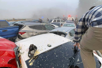 A person climbs over crashed cars at the scene of a multi-vehicle pileup in Virginia.