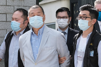 Jimmy Lai, second left, is led away from his residence by law enforcement officials in Hong Kong on Monday.