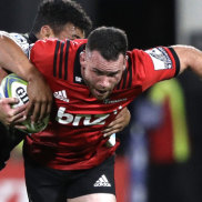 Crusaders star Ryan Crotty busts through the Hurricanes defence.