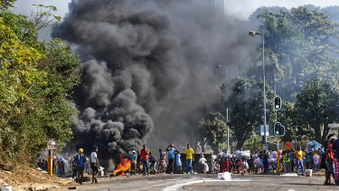 Looters outside a shopping centre alongside a burning barricade in Durban, South Africa.