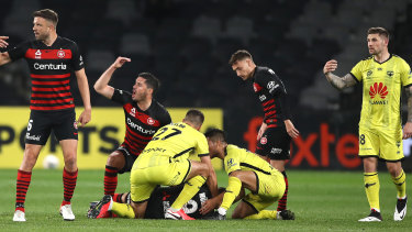 Wanderers players call for medical help after Nicolai Muller suffers a concussion against the Phoenix.