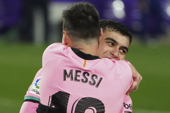"Barcelona's Lionel Messi celebrates with ""Pedri"" after scoring his side's third goal against Valladolid."