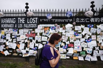 A woman passes a fence decorated with tributes to COVID-19 victims outside Brooklyn's Green-Wood Cemetery in New York.