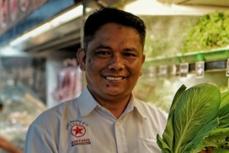 Bintang supermarket manager Kastrianto poses with fresh produce wrapped in banana leaves, not plastic.