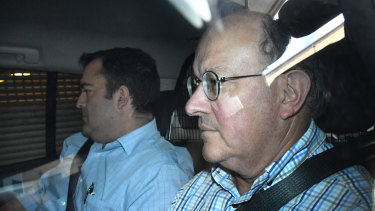 Dr William Russell Massingham Pridgeon (right) is seen being driven into the Brisbane Watchhouse after his arrest.